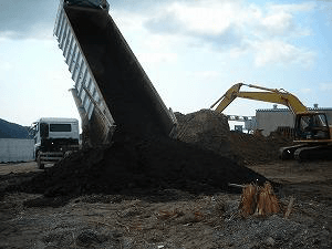 View of discharging compost and spraying EM・1® into the hole of organic waste